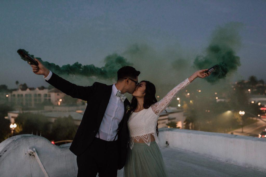 bride and groom kiss above Santa Ana holding smoke bombs