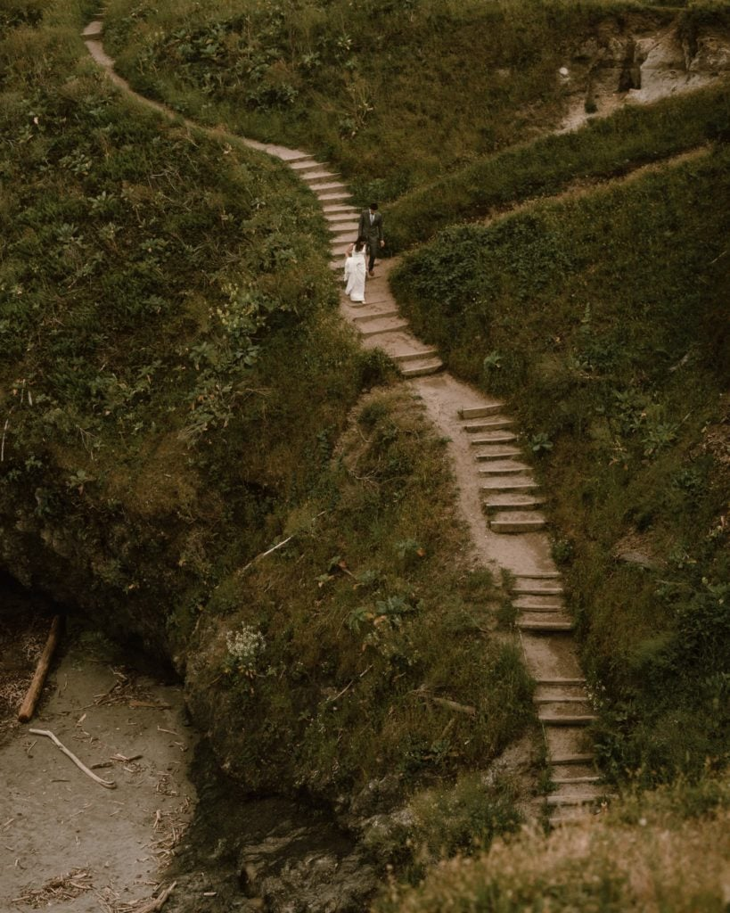 Eloping couple walks down sandy steps to the Mendocino beach
