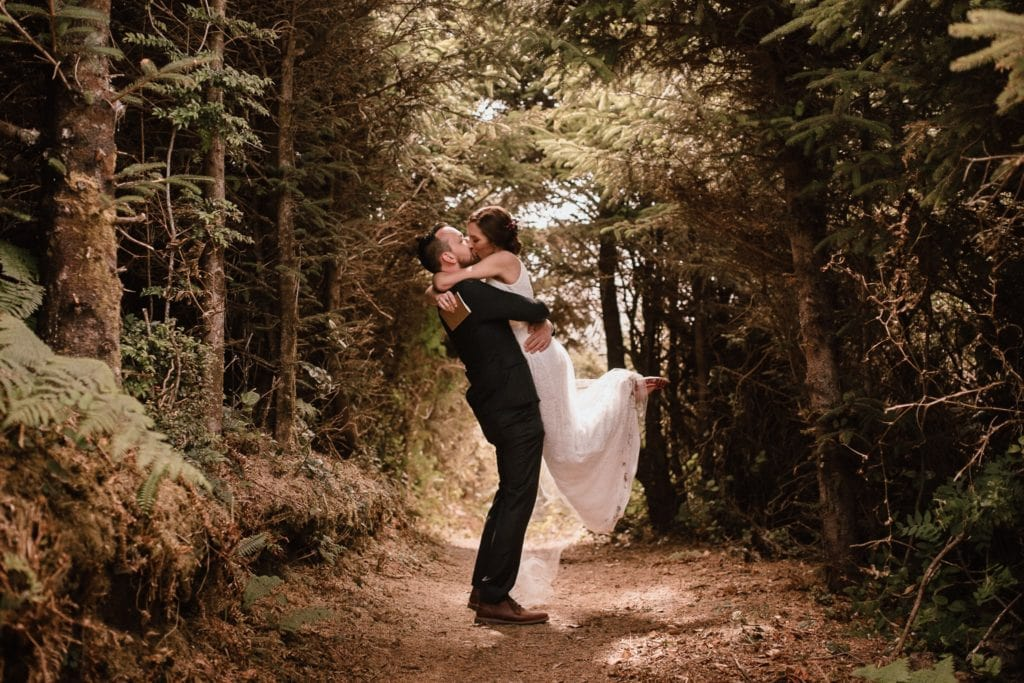 Bride and Groom kiss on trail along the Oregon Coast