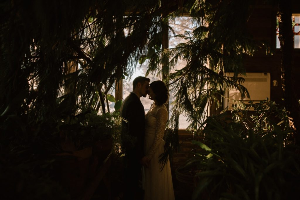 Silhouetted Bride and Groom kiss in the greenhouse at Windy Hill Farm, NC