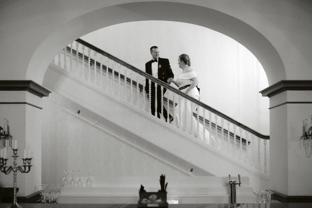 Bride and Groom walk up the stairs of the Inn on Broadway.
