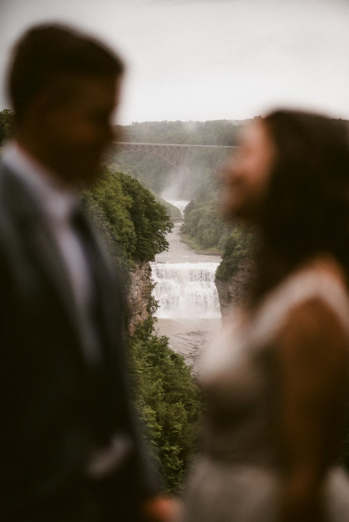 Blurry couple in foreground with Letchworth's Middle Falls in focus from Inspiration Point