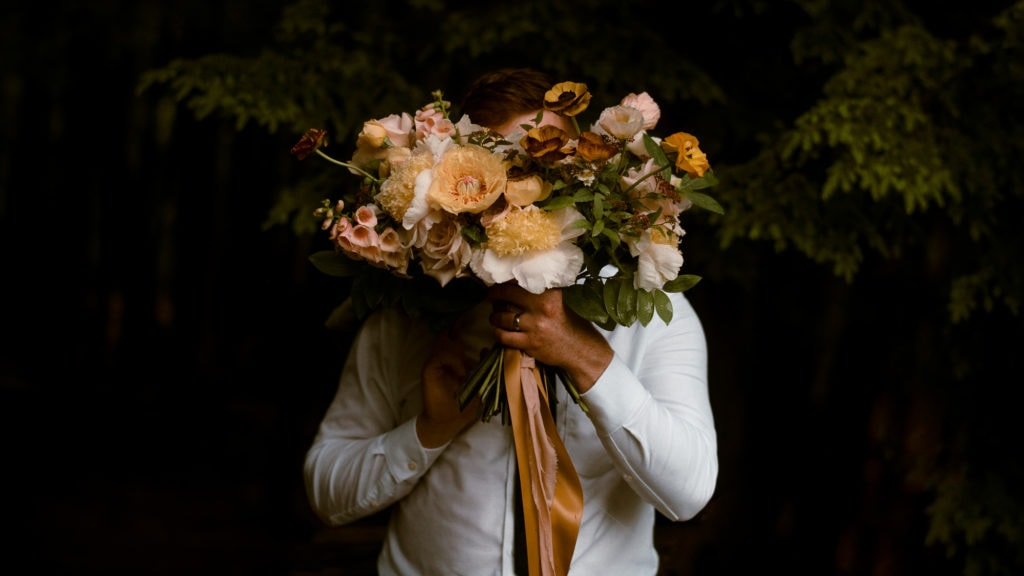 Groom holds bouquet in front of his face.