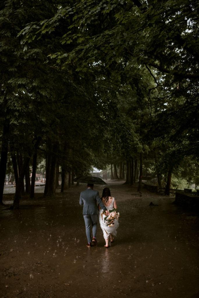 Bride and Groom walk in the rain under and umbrella.