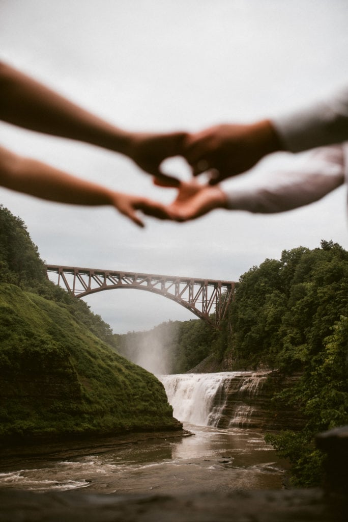 A couple hold hands with Letchworth's Upper Fall behind them.