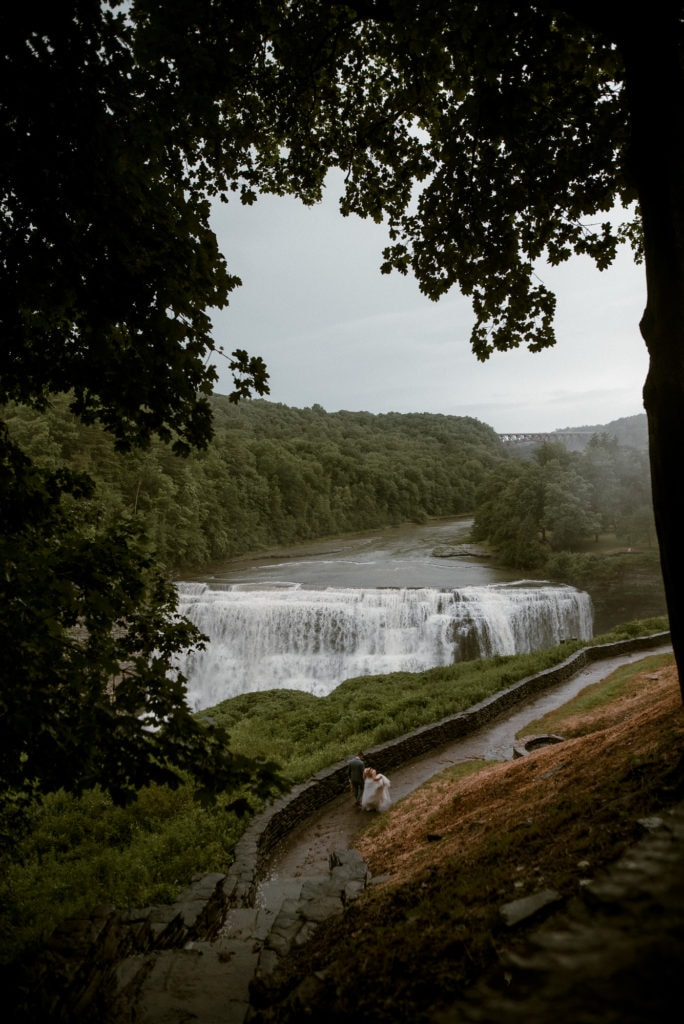 bride and groom walk away from the camera towards Middle Falls in Letchworth.